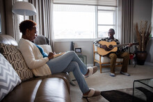Senior Couple Reading And Playing Guitar At Home