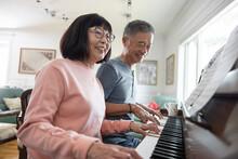 Senior Couple Playing Piano At Home