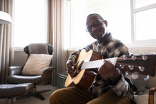 Portrait Of Senior Man Playing Guitar At Home