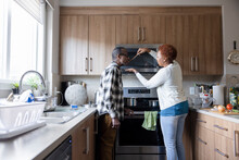 Senior Couple Cooking And Tasting Sauce In Kitchen