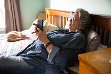 Senior Woman Using Phone On Bed