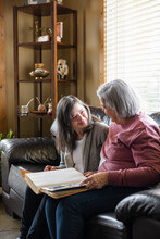Mother And Daughter With Down Syndrome Browsing Photo Album On Sofa