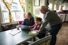 Grandparents Helping Granddaughter With Homework On Laptop