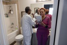 Senior Couple Brushing Teeth, Using Digital Tablet In Bathroom