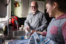 Grandfather And Granddaughter Washing Up At Kitchen Sink