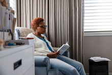 Senior Woman Reading Book In Armchair