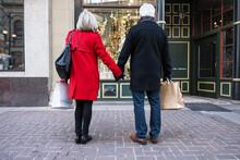 Senior Couple Holding Hands Window Shopping At Urban Storefront