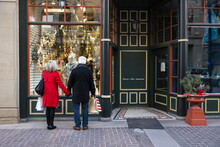 Senior Couple Looking At Christmas Display In Urban Storefront Window