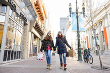 Mother And Teenage Daughter Holding Hands Shopping On City Sidewalk