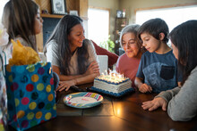 Family Celebrating Birthday Of Senior Woman At Home