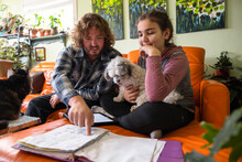 Man Helping Niece With Homework On Orange Sofa