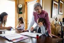 Grandmother Looking At Grandson Doing Homework At Table