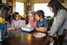 Family Celebrating Birthday Of Senior Woman At Home