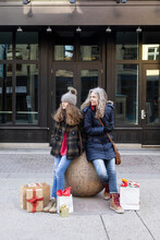 Mother And Daughter With Christmas Shopping Bags On Urban Sidewalk