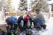 Father Helping Daughter With. Helmet At Snowy Backyard Ice Hockey Rink