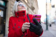 Senior Woman In Red Winter Coat Using Smart Phone On Sidewalk
