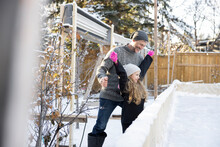 Father Watching Excited Daughter At Backyard Ice Rink
