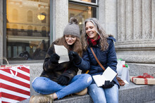 Mother And Teen Daughter Check Christmas Shopping List On Urban Ledge