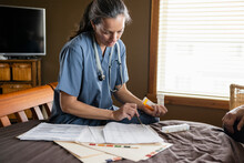 Nurse Checking Medical Records On Bed