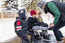 Mother Helping Son Put On Ice Skates At Backyard Ice Hockey Rink