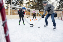 Family Playing Ice Hockey On Backyard Ice Rink