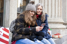 Mother And Teenage Daughter With Smart Phone And Christmas Shopping