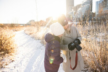 Mother And Daughter Using Camera In Sunny Snowy Winter City