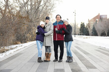 Portrait Happy Family In Winter Coats On Path In City Park