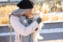 Happy Young Woman In Beret And Scarf With Small Dog