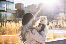Young Woman Holding Cute Small Dog In Sunny Urban Winter Park