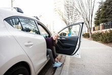 Portrait Woman Tying Shoelace From Car At Urban Curb