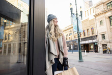 Thoughtful Blonde Woman Shopping In City In Winter