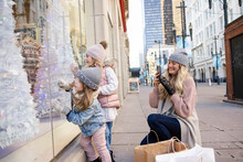 Mother And Daughters Looking At Christmas Tree Window Display In City