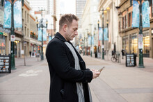 Man In Winter Coat And Scarf Using Smart Phone On City Street