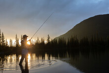 Silhouette Of Man Fly Fishing In Pond