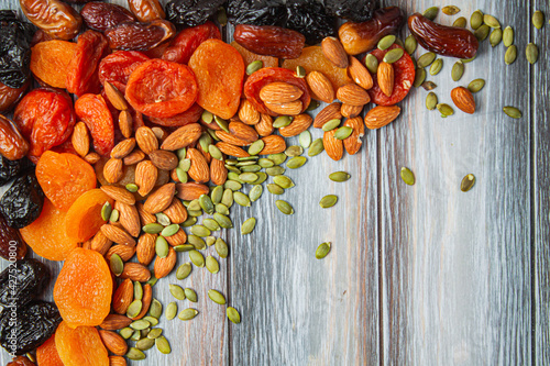 Bright frame of dried fruits and almonds and seeds on a light wooden background. Copyspace
