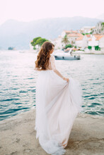 The Bride Stands On The Pier Near The Old Town Of Perast And Holds The Edge Of Her Skirt