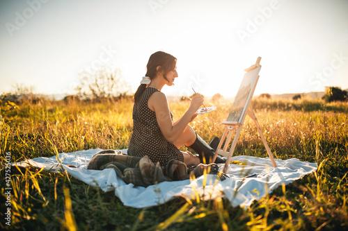 Giovane ragazza italiana dipinge il quadro in un prato di pomeriggio