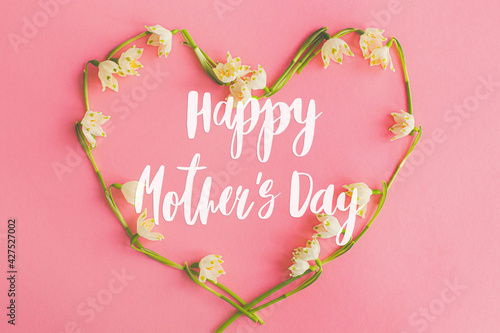 Obraz Happy mother's day. Happy mother's day text and floral heart flat lay on pink paper. Stylish floral greeting card. Handwritten lettering on heart made of spring flowers on pink. Mothers day - fototapety do salonu