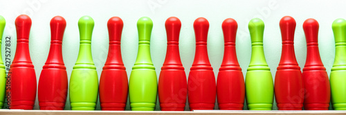 Vászonkép Red and green colored plastic skittles stand in row in gymnasium or school