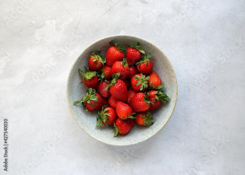 Fotografie, Obraz Fresh strawberries in a ceramic plate on a concrete background