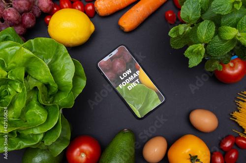 Telefon z tekstem low FODMAP diet na ekranie, otoczony warzywami i owocami, zdrowa dieta i odżywianie - fototapety na wymiar