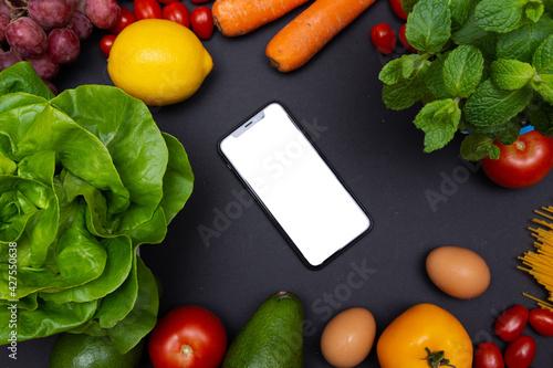 telefon z białym ekranem i miejscem na tekst, otoczony warzywami i owocami, zdrowa dieta i odżywianie