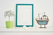 Green Mock Up Picture Frame On White Shelf With Wooden Boat And Decorative Tree Made Of Natural Semi-precious Stones On White Wall; Portrait Orientation; Stylish Interior Bright Background