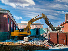 Excavator At Demolition Site In The City Demolishing A Building.
