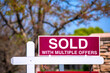 SOLD With Multiple Offers real estate sign near purchased house indicates hot seller's market in the desired neighborhood. Blurred outdoor background
