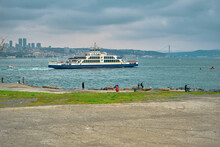 04.03.2021. Istanbul Turkey. Pedestrian Ferry Passing In Bosporus Istanbul Near Sarayburnu District With Many People Walking And Fishing In Sea Shore During Overcast Weather With City Silhouette