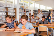 Upset Serious Boy And Girl Reading Books During Lesson In Classroom