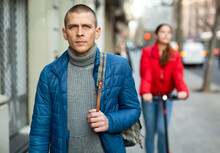 Portrait Of Handsome Serious Young Man In Blue Jacket Walking Autumn Street