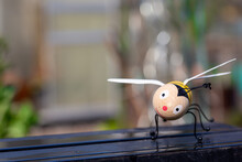 Wooden Bee Figure With Happy, Smiling Face In Unusual Spring Weather With Rain And Copyspace For Text On Left Side